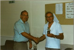 Photograph of Stan receiving the 1996 trophy from the 1995 champion