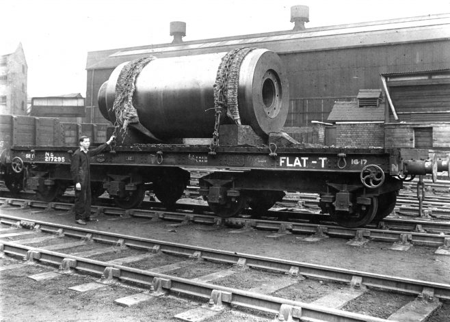 RT005 This view is taken from the railway sidings with Hydraulic 1 shop in the background.  It is of a very large main ram loaded on trail transport. Ed note: The size of the ram suggests to me it may have been destined for the 5000 ton extrusion press for Rogerstone (the largest press built at the time) in which case it would be around 1939/40s era.