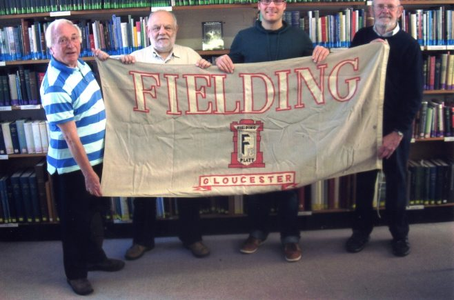 Photo 82. Brian Mince; Jeff Hogg; Ollie Taylor; John Davis. Displaying the 'Fielding' flag at the Gloucestershire Archives.